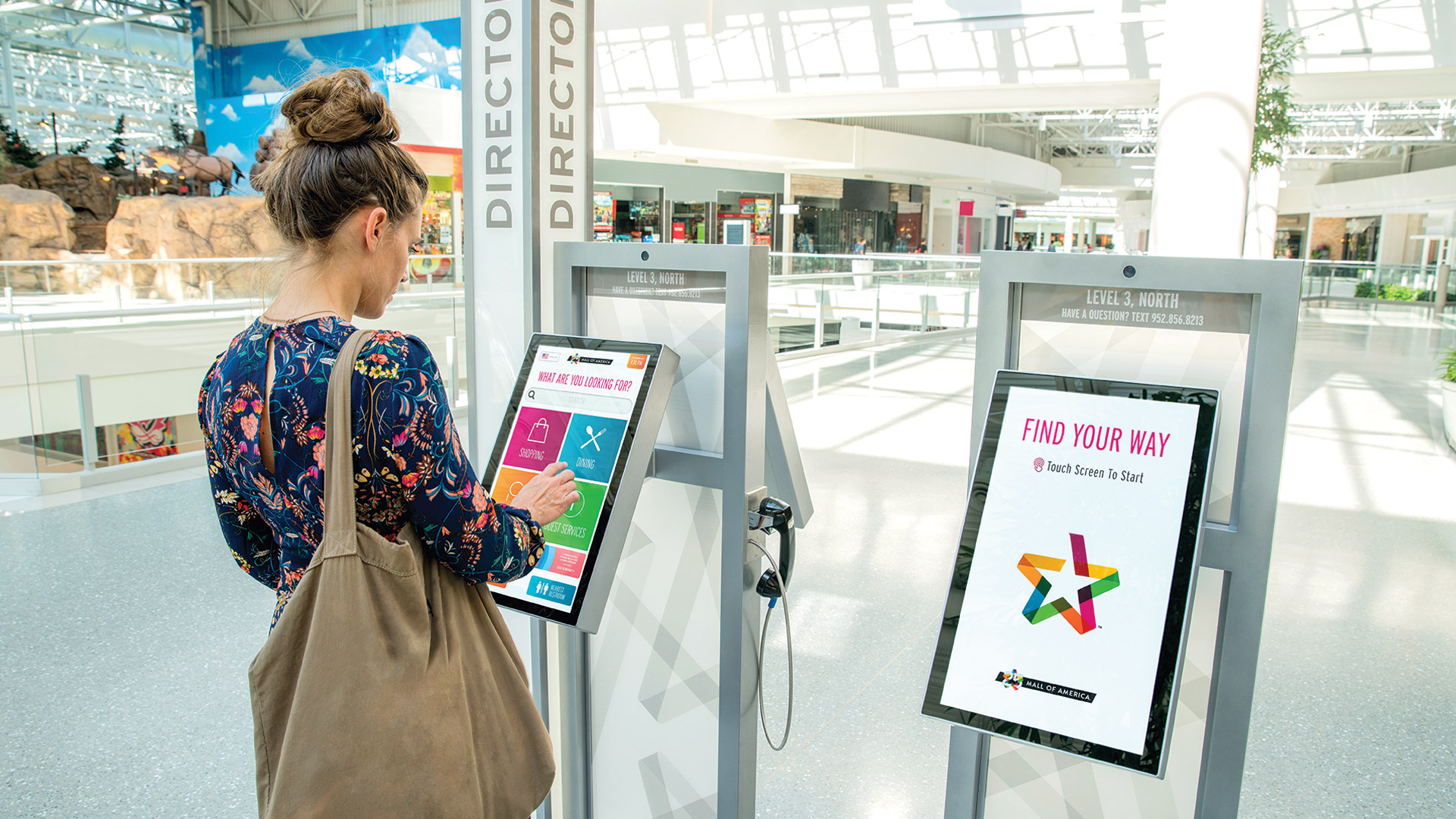 Girl using an interactive wayfinding kiosk at the Mall of America