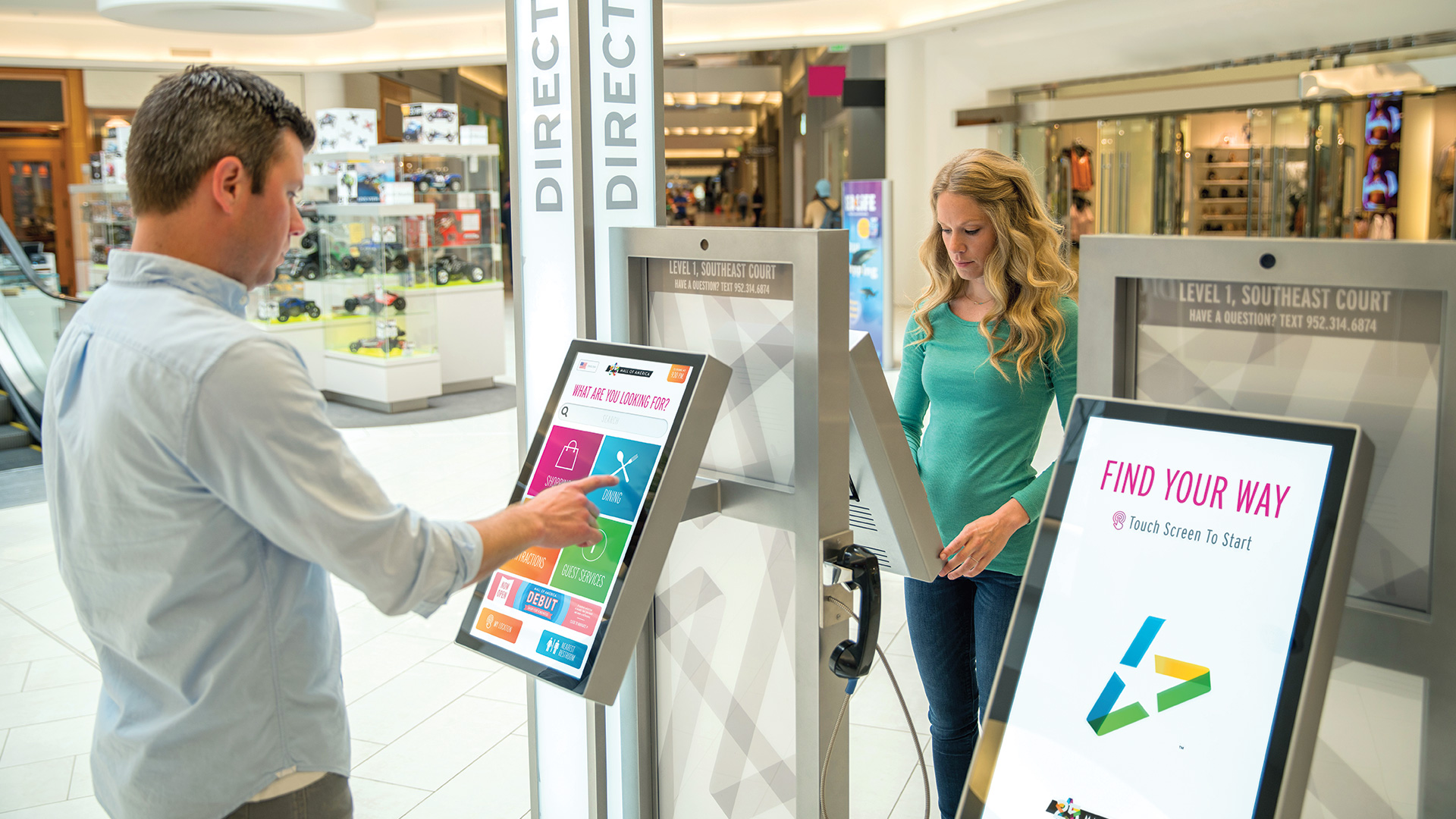 A guy and a girl standing across from each other using the interactive wayfinding kiosks at the Mall of America