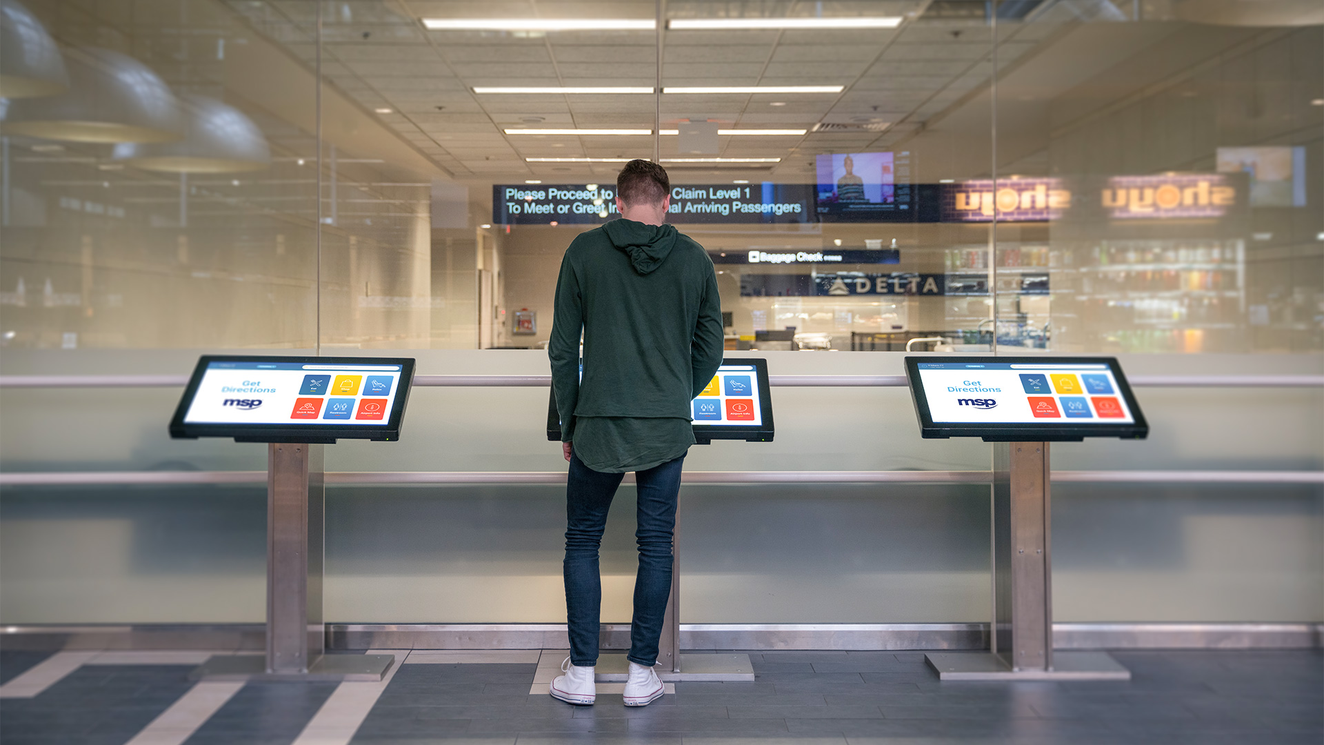 A guy using the middle interactive wayfinding kiosk at the MSP Airport