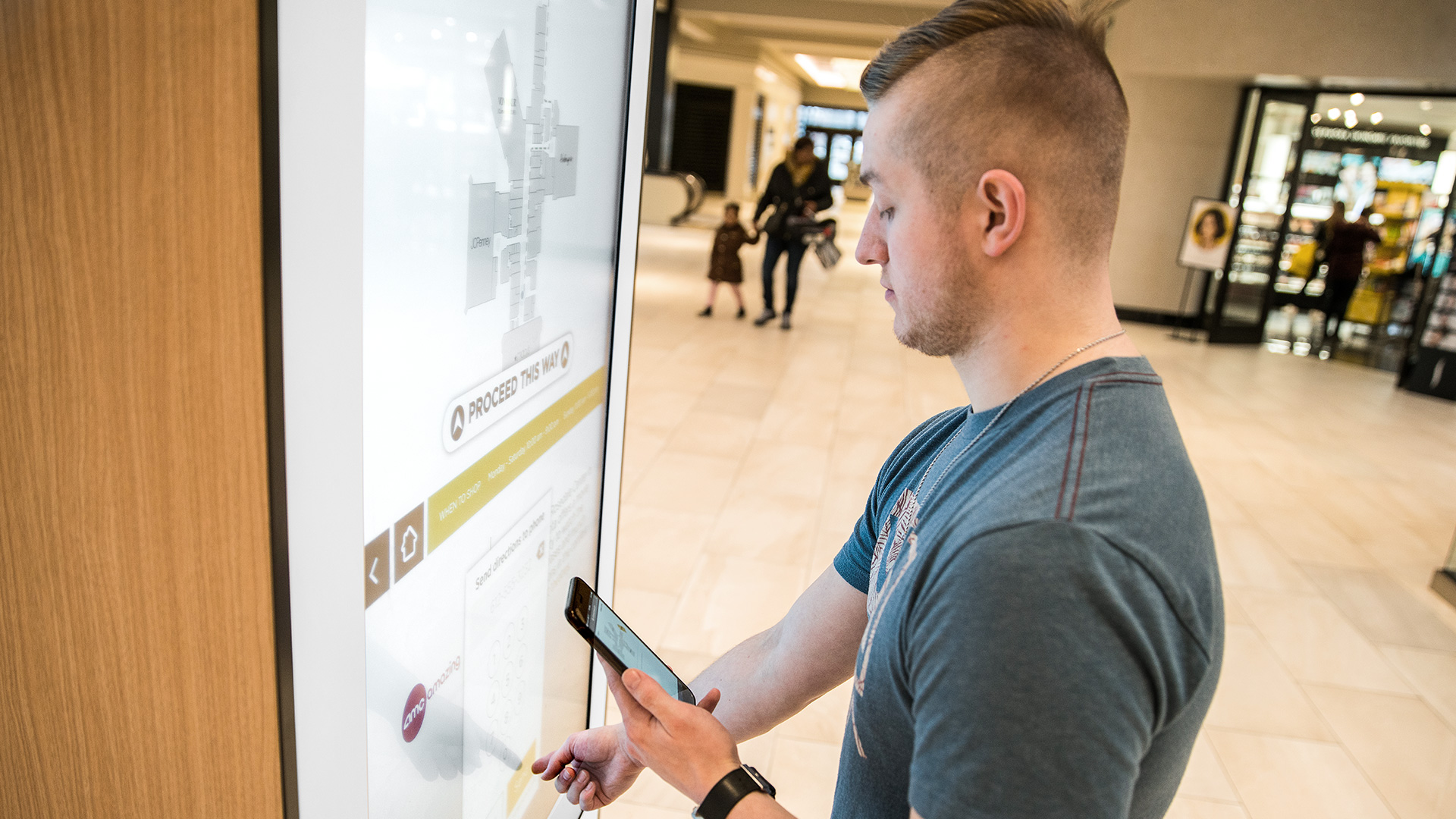 A guy using the interactive wayfinding kiosk at the Rosedal Center