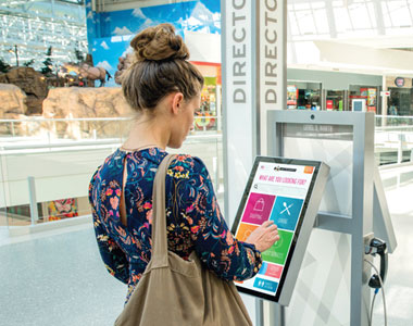 a women looking at an interactive wayfinding kiosk.