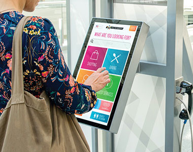 Close up shot of a women using an interactive wayfinding kiosk.