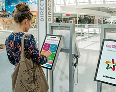 A girl using an interactive wayfinding kiosk.